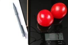 Controle de peso - escala de vidro preta da cozinha com tomates, o lápis e papel vermelhos Fotografia de Stock Royalty Free