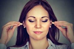 Controle de ruído Jovem mulher com tomadas da orelha foto de stock