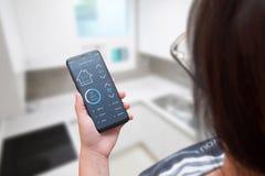 Controle home esperto app do uso da mulher no telefone celular moderno fotos de stock royalty free