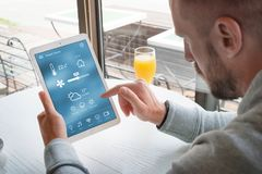 Controle home esperto app na exposição do portátil nas mãos do homem imagem de stock