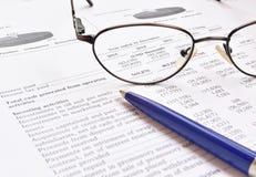 Controle van financieel verslag, glazen en pen Royalty-vrije Stock Foto's