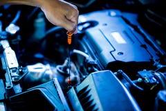 Controleer het olieniveau in motor van een auto Mechanisch het controleren motor van een auto of voertuig royalty-vrije stock afbeeldingen