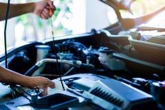 Controleer het olieniveau in motor van een auto Mechanisch het controleren motor van een auto of voertuig stock foto