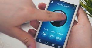 Controlerende temperatuur in het huis die smartphone app gebruiken stock videobeelden