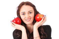 Controles adolescentes de la muchacha cerca de las manzanas de la cara Imagen de archivo