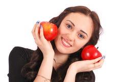 Controles adolescentes de la muchacha cerca de las manzanas de la cara Imagen de archivo libre de regalías