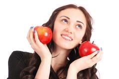 Controles adolescentes de la muchacha cerca de las manzanas de la cara Foto de archivo libre de regalías