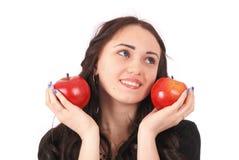 Controles adolescentes de la muchacha cerca de las manzanas de la cara Fotos de archivo