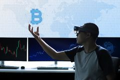 Controles Bitcoin dos homens no mundo da realidade virtual Fotografia de Stock Royalty Free