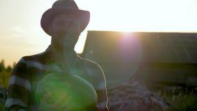 Controles caucásicos del sombrero de In A del granjero del hombre en sus manos una sandía madura en la puesta del sol almacen de video