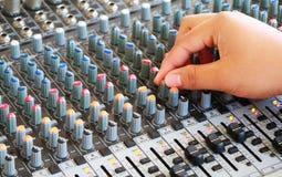 Controles de la consola de mezcla audio con la mano Fotos de archivo libres de regalías