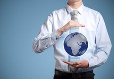 Controles del hombre de negocios o sostener la tierra del mundo disponible Fotografía de archivo