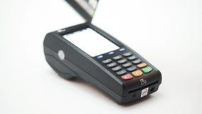 Controles a disposición una tarjeta de crédito delante del terminal del fondo blanco