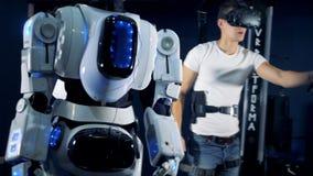 Controles do homem um robô, usando o equipamento de VR, fim acima