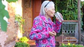 Controles mayores de las manos los más viejos hacen tabletas el agua de las bebidas almacen de video
