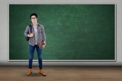 Controles mochila y libro del estudiante masculino Foto de archivo libre de regalías