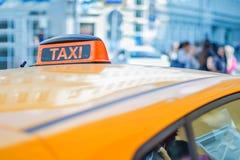 Controleurstaxi op het dak van een gele auto in het centrum van een grote stad Stock Foto