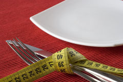 Controling obesity. Fork and knife tieup with a measure tape. Conceptual idea of controling obesity. (selective and soft focus Stock Photography
