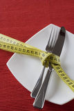 Controling obesity. Fork and knife tieup with a measure tape. Conceptual idea of controling obesity. (selective and soft focus Royalty Free Stock Photo