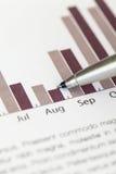 Controllando il diagramma di vendite annuali con la penna di ballpoint Fotografia Stock