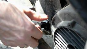 Controllando il livello di olio per motori in un motociclo, un uomo svita la valvola video d archivio
