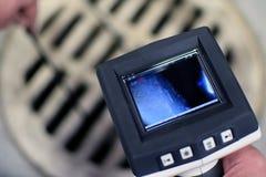Controllando la botola della fogna con la macchina fotografica di ispezione di periscopio fotografia stock