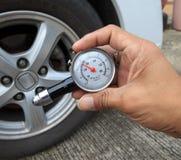 Controllando pressione d'aria della gomma con il calibro del tester prima del viaggio Fotografia Stock