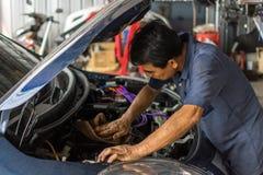 Controllando un motore di automobile per vedere se c'è la riparazione al garage dell'automobile fotografie stock libere da diritti