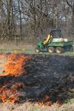 Controlled Burning. Employees of the Macon County Conservation District are performing a controlled burn on an early spring morning. They use a burn pot filled stock photo