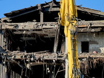 The controlled demolition of a house. Demolishing the building using a machine Stock Photo