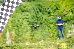 Controlled unmanned drone in flight in summer,. Dron is controlled by a pilot in a helmet Stock Photography