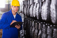 Controller checking gumboots. Factory quality controller checking gumboots in warehouse Stock Images