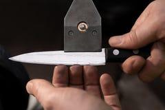 Controlli il coltello affilato per vedere se ci sono sbavature fotografia stock libera da diritti