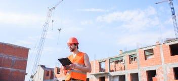 Controlli il processo della costruzione Tipo nel supporto protettivo del casco davanti a costruzione fatta dai mattoni rossi Aran fotografia stock