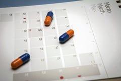 Controlli le pillole su un calendario Fotografia Stock