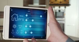 Controlling lights in the apartment using digital tablet. Man controls light in the apartment using smart home application on his digital tablet stock video