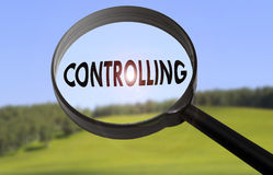Controlling. Magnifying glass with the word controlling on blurred nature background Royalty Free Stock Photo
