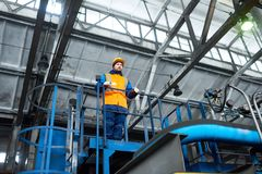 Controlling Production Process at Modern Plant. Low angle view of handsome young worker wearing uniform and protective helmet looking at spacious production Royalty Free Stock Photo