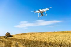 Controlling a remote helicopter drone. Drone flight. Controlling a remote helicopter drone. Drone flying over fields royalty free stock image