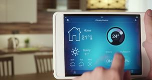 Controlling temperature in the house using app on the digital tablet. Man controls temperature in his apartment using smart home application on his digital stock video footage