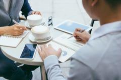 Controllo degli stock Due soci commerciali che lavorano al computer portatile che sorride allegramente su una riunione al caff? l fotografia stock libera da diritti