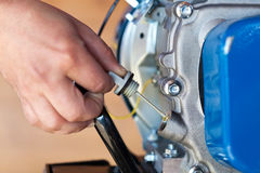 Controllo del livello di olio su un piccolo motore a combustione Immagine Stock