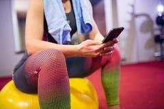 Controllo del telefono alla palestra Immagine Stock
