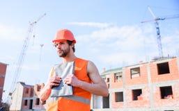 Controllo dell'appaltatore secondo il piano Supporto protettivo del casco del tipo davanti a costruzione fatta dai mattoni rossi  fotografia stock