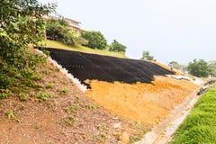Controllo dell'erosione del pendio con le griglie e terra sul pendio ripido immagine stock