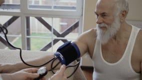 Controllo dell'uomo senior il suo impulso alla ricezione del ` s di medico video d archivio
