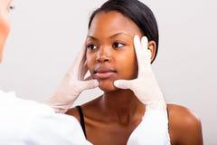 Controllo della pelle di medico Immagine Stock