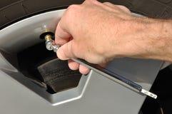Controllo della pressione d'aria di una gomma Fotografia Stock