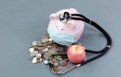 Controllo della salute dell'economia con il porcellino salvadanaio e medico fotografia stock libera da diritti