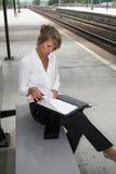 Controllo delle sue note al trainstation Fotografie Stock Libere da Diritti